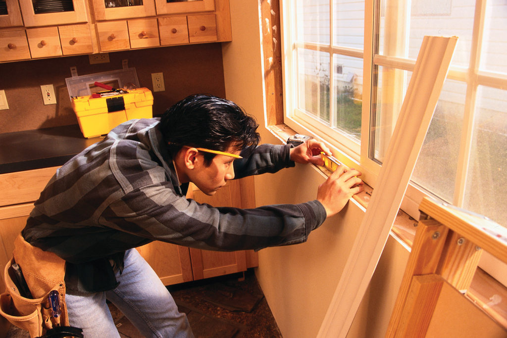 Builder remodeling a kitchen window.